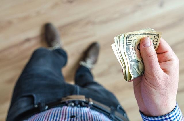 bankovky v ruce, pohled na nohy shora.jpg