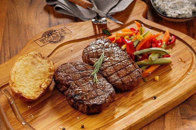 steak se zeleninou a přílohou na dřevěném podnose v restauraci